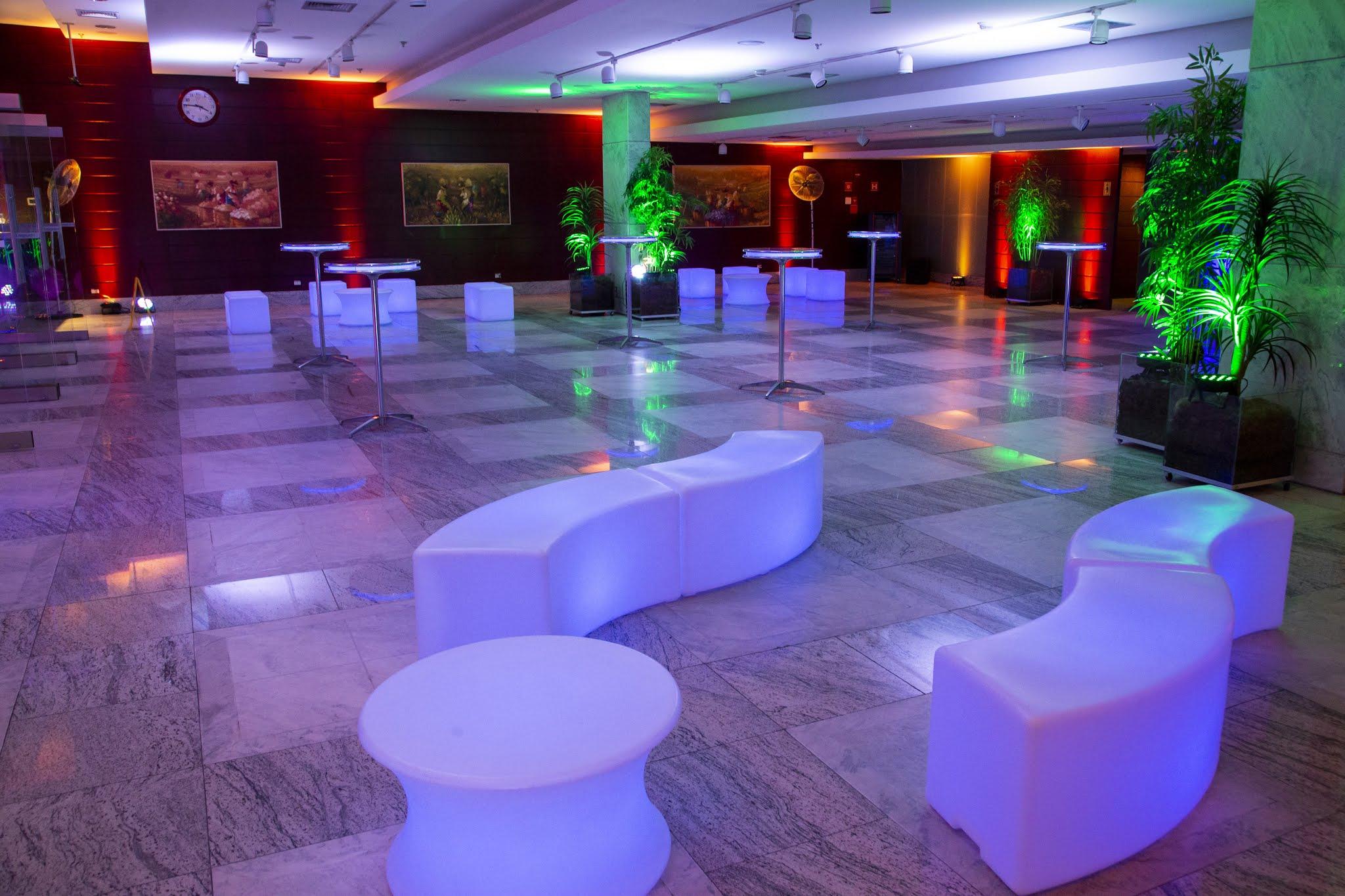 Foto do ambiente Foyer (Salão de Eventos), com um amplo espaço, iluminação estilizada etilizada em tonalidade roxa e verde onde existem os vazos