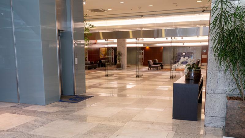 Foto da entrada do Foyer (Salão de Eventos), com um elevador à esquerda e o amplo espaço ao fundo