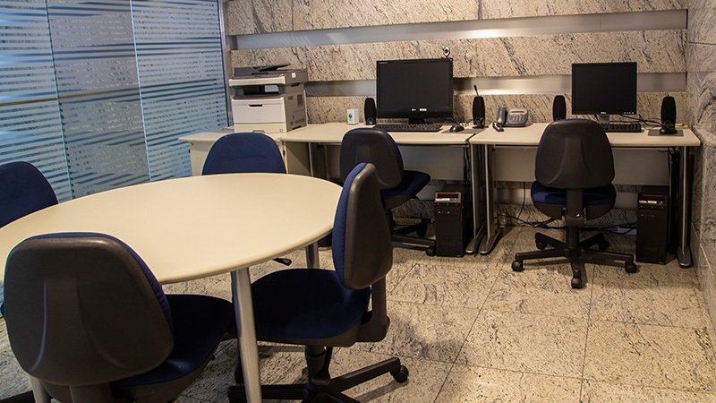 Sala de apoio do Teatro CIEE, com uma mesa redonda e cadeiras ao redor. Ao fundo, uma impressora e dois computadores