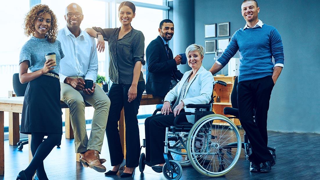 cinco funcionarios sorridentes ao lado de um cadeirante