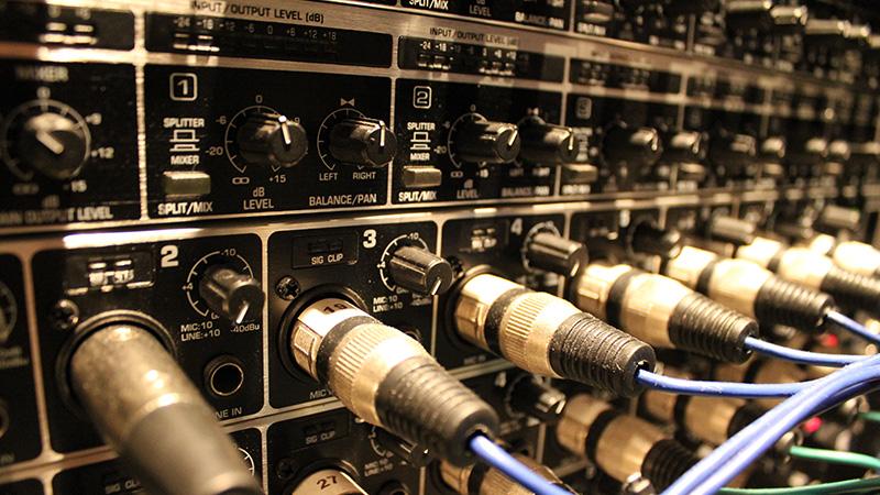 Foto de um equipamento de áudio com diversos cabos conectados