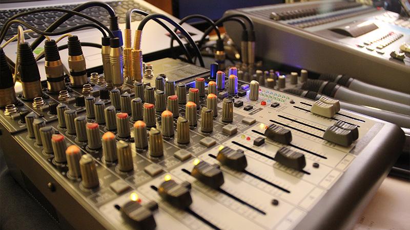 Foto de um equipamento de áudio com diversos botões e cabos conectados.