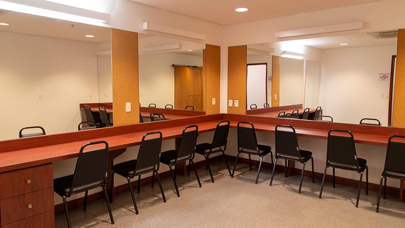 Foto mostrando o espaço dos camarins do Teatro CIEE. Conta com grandes espelhos, mesa de apoio e diversas cadeiras