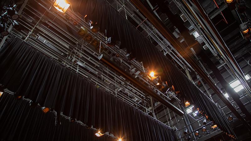 Foto mostrando os diversos equipamentos, como vestimentas cênicas, iluminação na parte superior do palco.