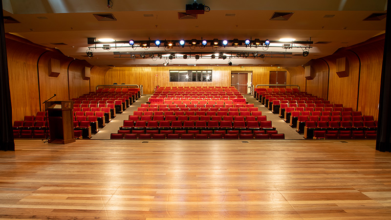 Foto tirada do palco, mostrando ao fundo as portas de acesso, janelas da sala de controle e as cadeiras vermelhas do Teatro CIEE