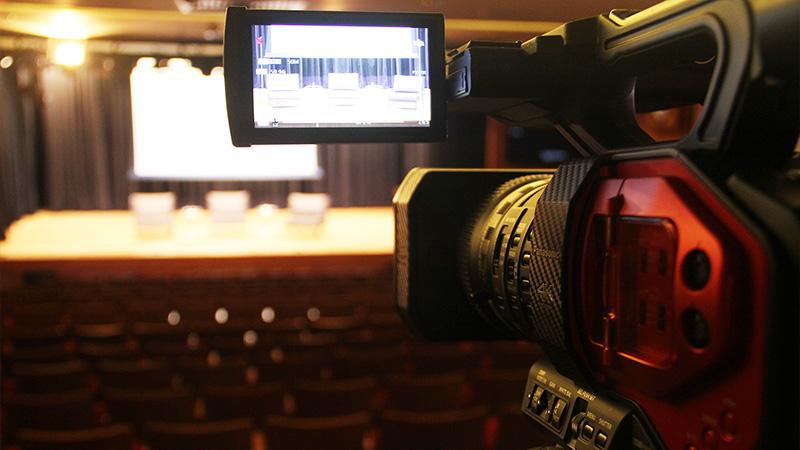 Foto de uma câmera de filmagem em primeiro plano apontada para o palco do Teatro CIEE