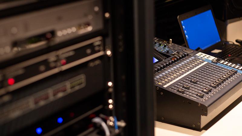 Foto de equipamentos na sala de controle do Teatro CIEE, mostrando ao fundo uma mesa com diversos botões e um notebook