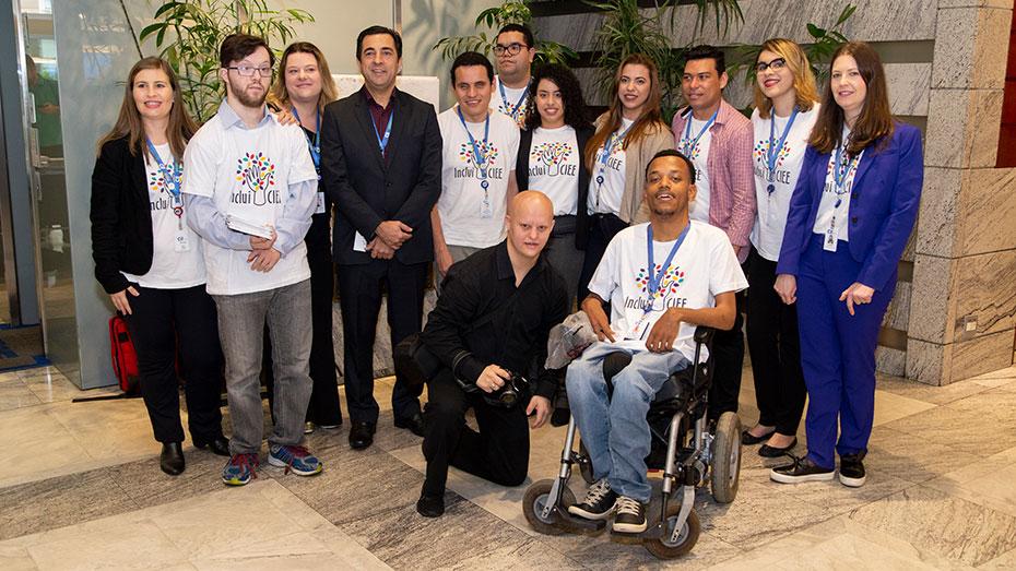 Treze participantes do evento e da equipe do Inclui CIEE, sendo um deles cadeirante, retratados de frente no local do evento.