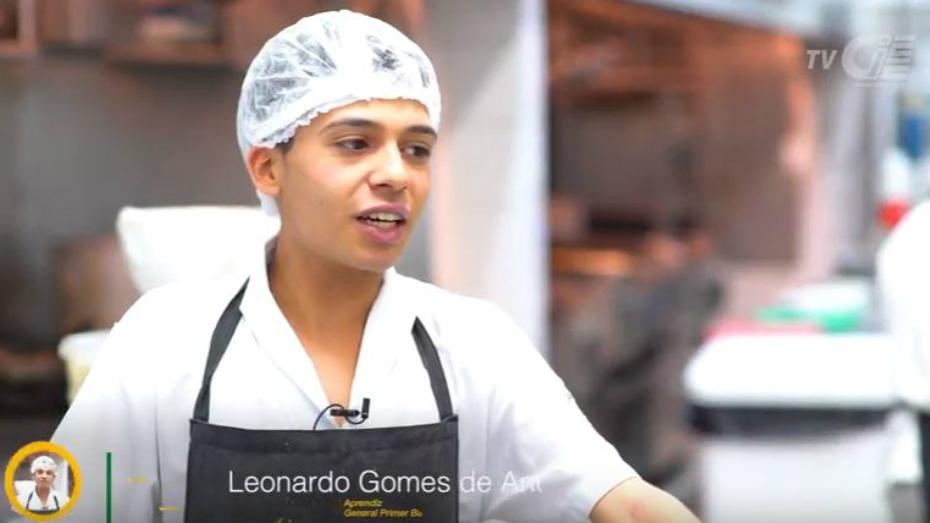 Jovem aprendiz Leonardo Gomes retratado de frente, usando touca e uniforme de cozinha.