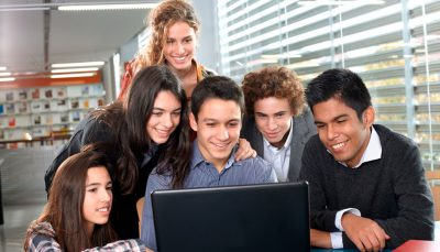 Grupo de seis jovens olhando para tela de um computador