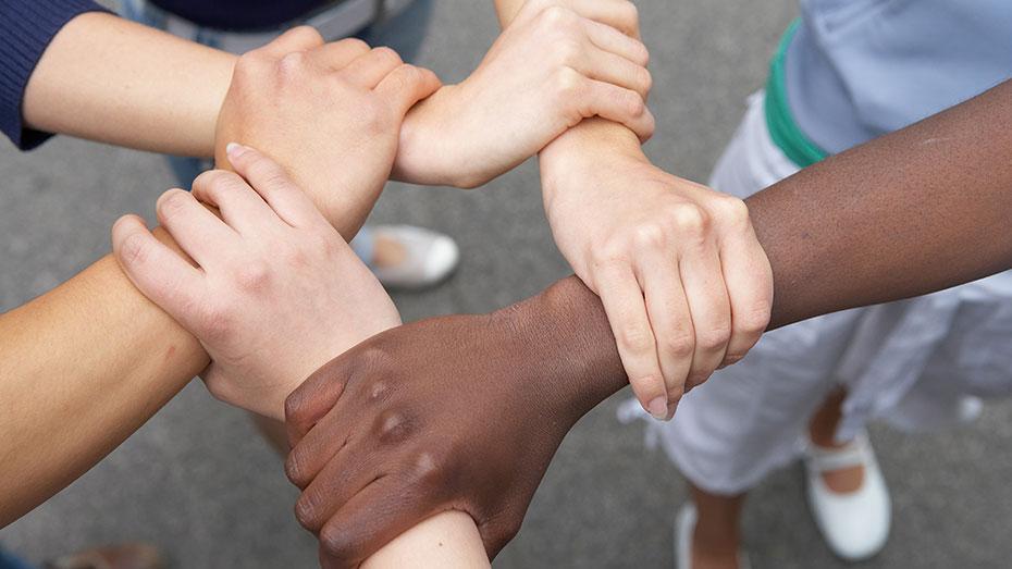 Destaque para cinco mãos de pessoas de diferentes etnias unidas vistas de cima.