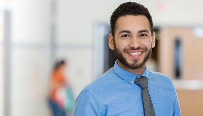 jovem sorridente vestindo uma camisa azul e gravata cinza no centro da imagem. O fundo está desfocado