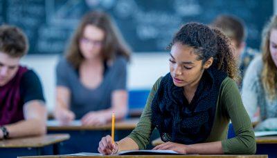 Cinco jovens, sentados em uma sala de aula, fazem uma prova escrita