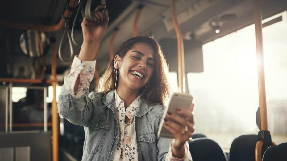 Moça jovem em pé dentro de um ônibus de dia segura celular em uma das mãos e sorri