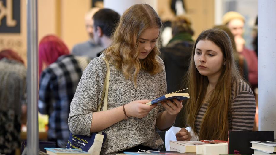 Duas adolescentes em primeiro plano olham livros em um estande de feira