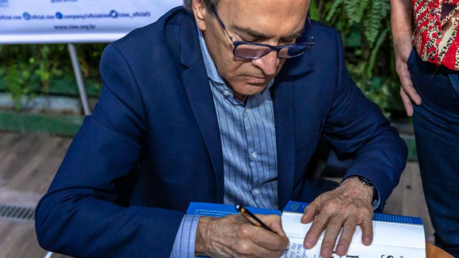 Theunis Marinho de terno azul, autografando seu livro