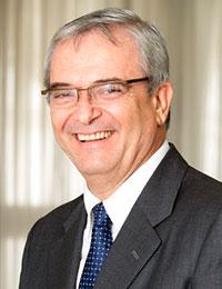 Foto de homem em perfil sorrindo com cabelos grisalhos, de terno cinza, gravata azul e utilizando óculos