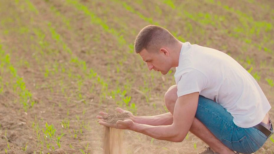 Jovem agachado no campo segurando um punhado de terra na mão enquanto olha para ela.