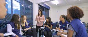 Instrutora em pé entre diversos estudantes no Programa Aprendiz Legal