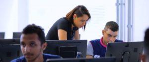 Instrutora oferecendo orientações a um estudante em frente ao computador