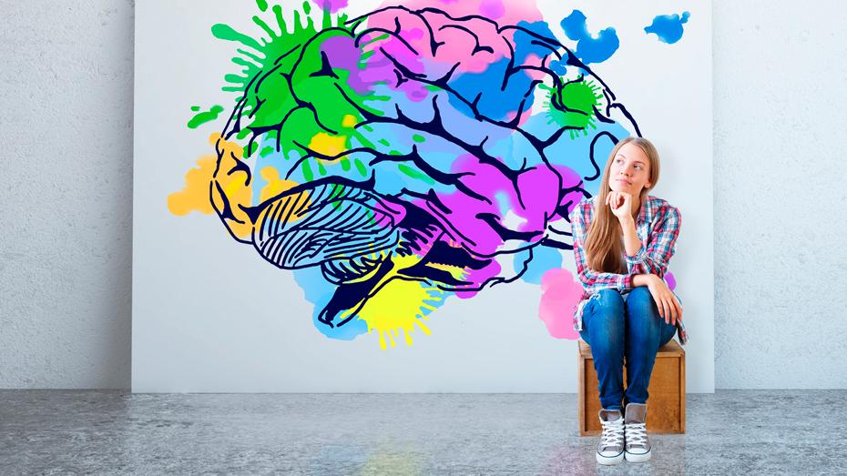 Garota sentada e observando um quadro ao fundo com uma ilustração de um cérebro com diversas partes coloridas