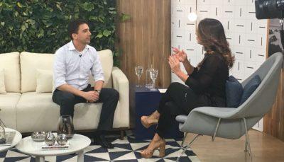 Alexandre Altenfelder, supervisor de Feiras do CIEE, sentado em sofá, conversa com Claudia, apresentadora, em poltrona que está em sua diagonal