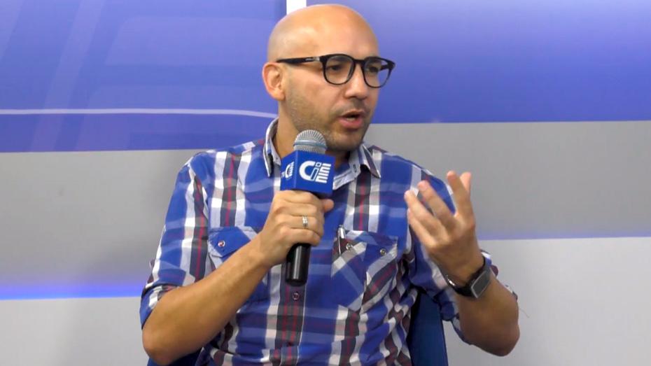 Homem de pele clara e óculos de aros grossos segura um microfone com a logomarca do CIEE e fala enquanto gesticula. Ele veste uma camisa quadriculada azul