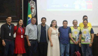 Seis homens e duas mulheres abraçados na frente de um auditório sorriem e posam para a foto