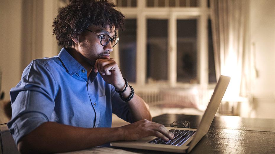 Jovem negro em sua casa trabalhando em um laptop