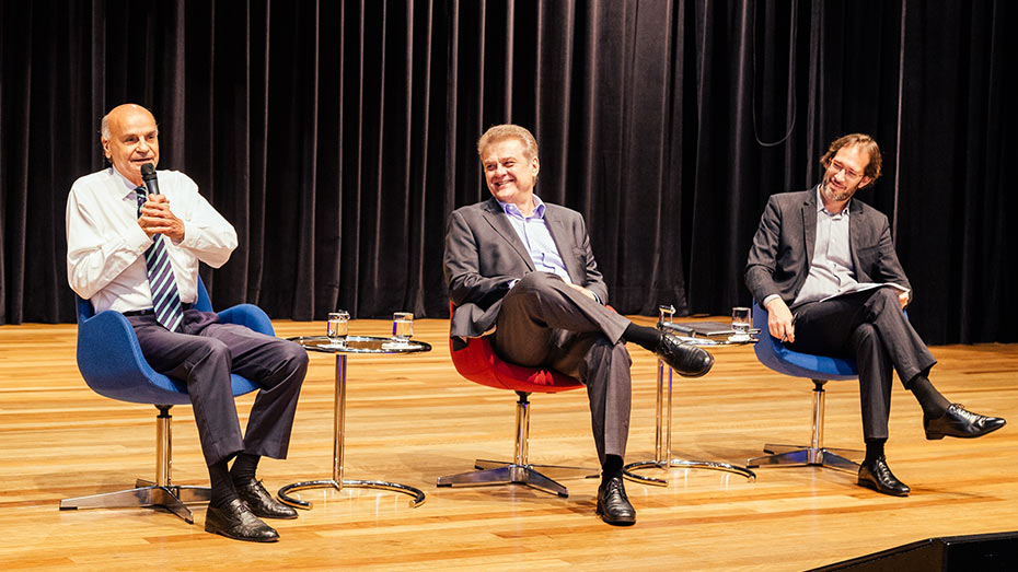 Palco do Teatro CIEE onde temos visão frontal dos três palestrantes sentados, da esquerda para a direita vemos o doutor Dráuzio Varella segurando o microfone e Humberto Casagrande e Pierpaolo Bottini .