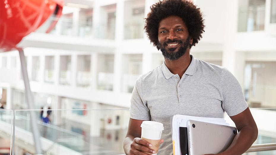 Homem negro, por volta dos 40 anos, com café em uma mão e notebook e livros em outra
