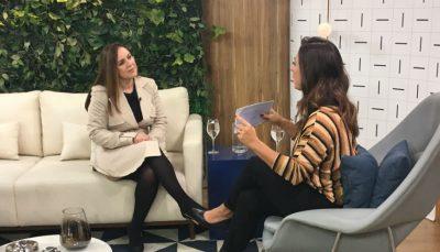 Ana Martins, conversar com Claudia, apresentado do programa. Ana está sentada em um sofá e Claudia em uma poltrona a sua frente
