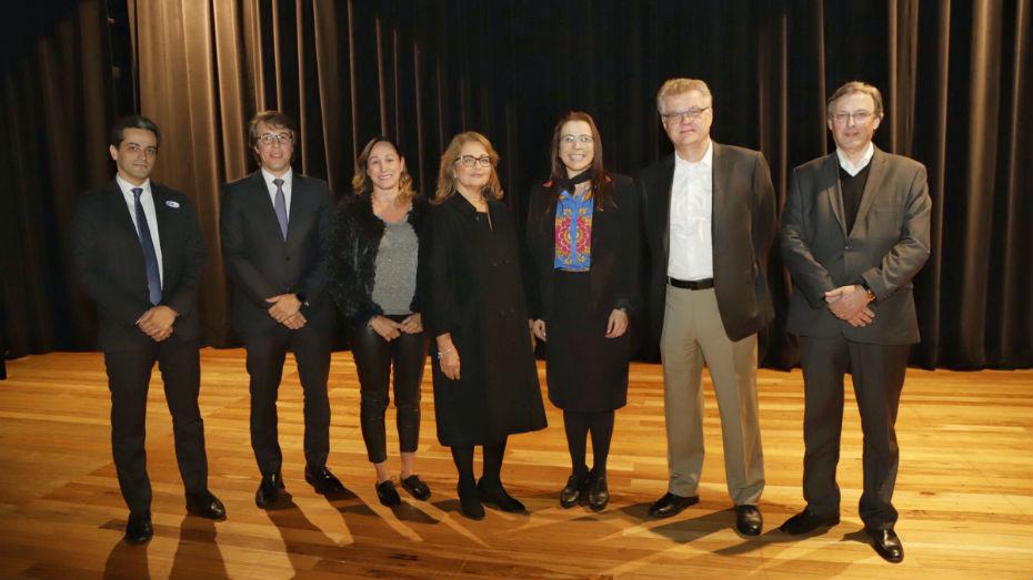 Participantes de seminário sobre aprendizagem posam para foto no palco do teatro CIEE