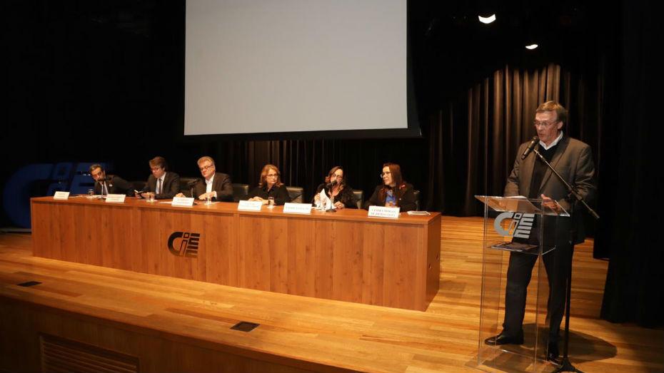 Ricardo Melantonio ao microfone, demais palestrantes posicionados na mesa diretora do evento