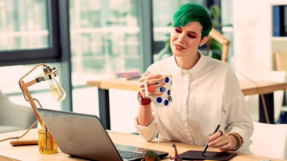Mulher sentada em uma mesa sorri para a tela do notebook enquanto bebe chá