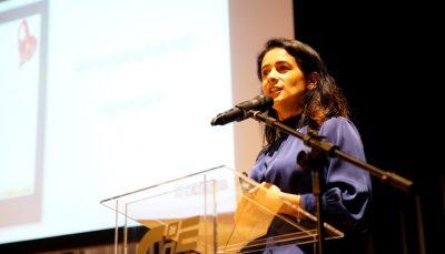 mulher vestida de azul, falando ao microfone em palco