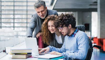 Estudante cadeirante em frente ao notebook e ao seu lado estão um homem e uma jovem