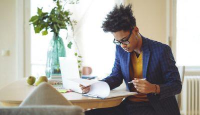 Homem de terno sentado em mesa está lendo e anotando em algumas folhas de papel