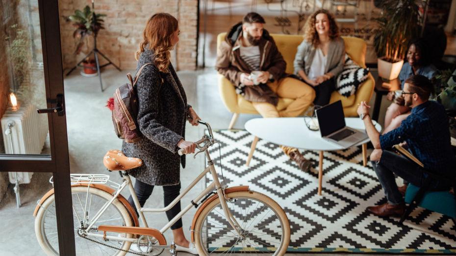 Uma mulher com uma bicicleta na mão em uma sala com quatro pessoas, duas mulheres e dois homens, sentados em sofá
