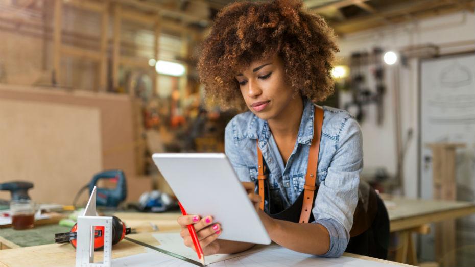 Mulher em oficina está apoiada sobre balcão e mexendo em um tablet