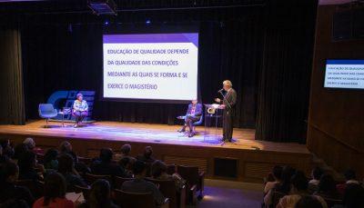 Plateia acompanha seminário com dois homens e uma mulher no palco