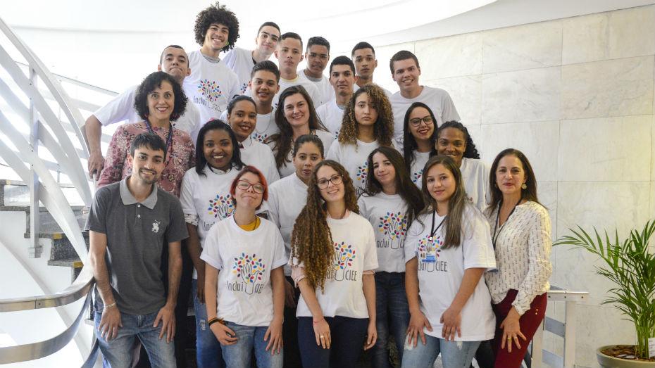 Grupo de estagiários e aprendizes PCDs posam alegres para foto em escadaria