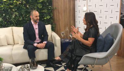 Marcelo Paschoal, sentado em sofá no cenário do programa Vida Melhor, conversa com Claudia, sentada em sua diagonal
