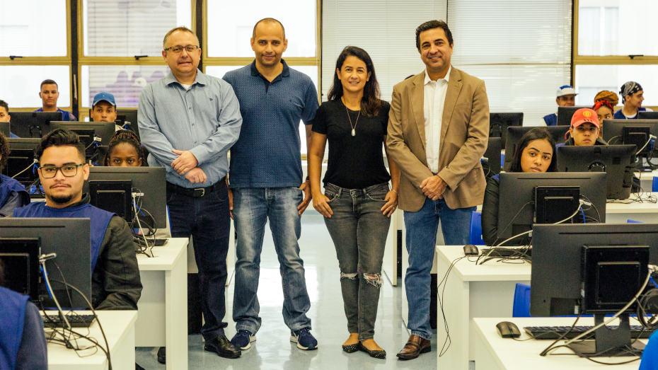 sala de capacitação com aprendizes utilizando computadores e quatro profissionais do CIEE e ACREFI em pé lado a lado