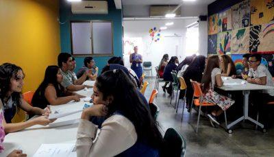 sala com jovens sentados em duas mesas, com orientadora social ao fundo
