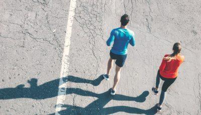 Vista de cima de um homem de azul e uma mulher de laranja praticando corrida lado a lado