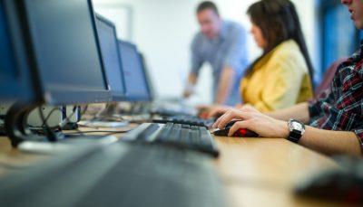 mesa com jovens digitando no computador