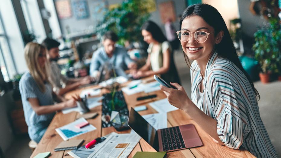 Menina sorrindo em mesa de trabalho compartilhada com outras quatro pessoas que estão ao fundo
