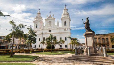 Imagem de praça com igreja branca colonial ao fundo em dia ensolarado