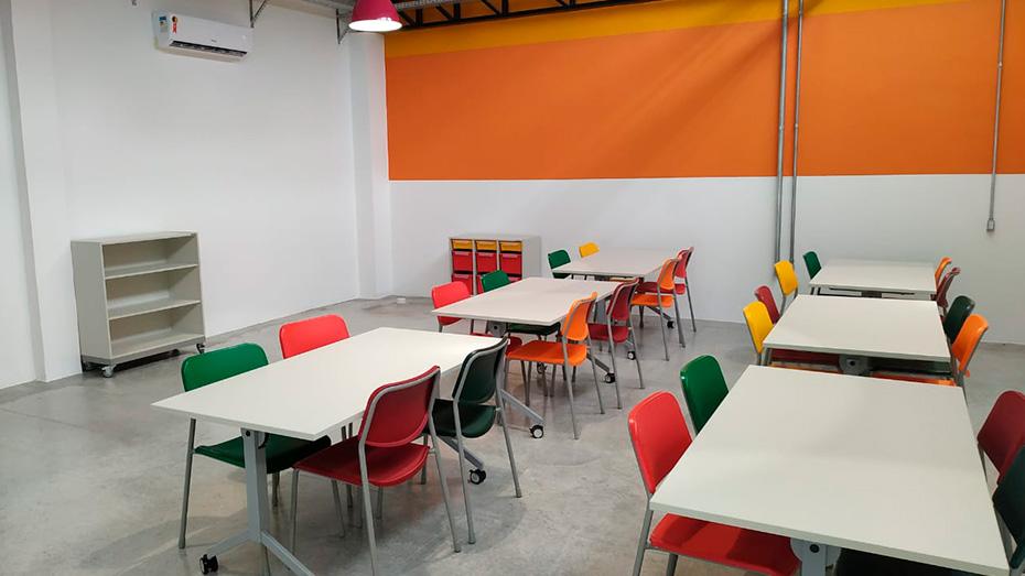 Ambiente com mesas brancas e cadeiras coloridas